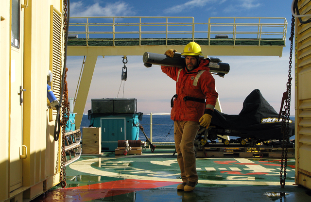 Man carries instrument on ship deck.