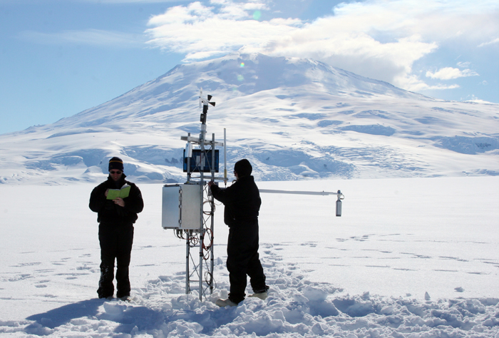 Scientists install instrument on automatic weather station.