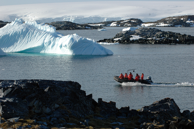 People navigate boat through icebergs.