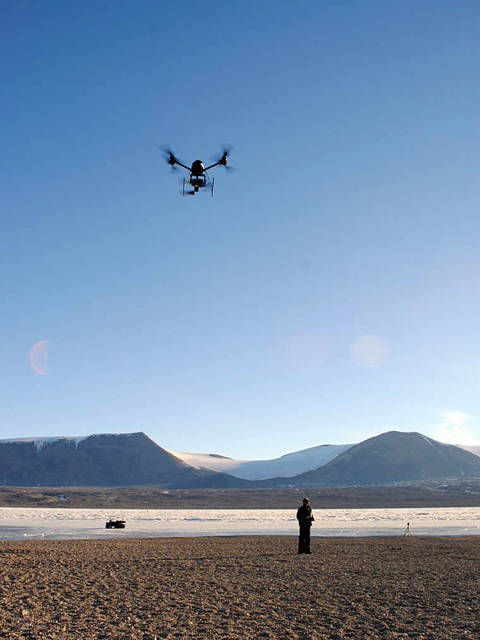 Person operates remote-control helicopter.