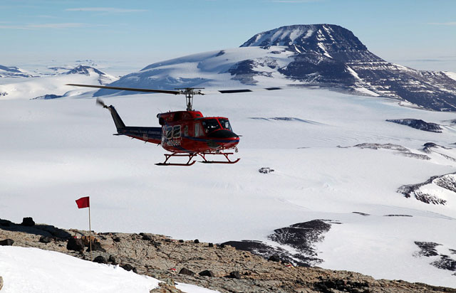 Helicopter flies near snow-covered mountains.