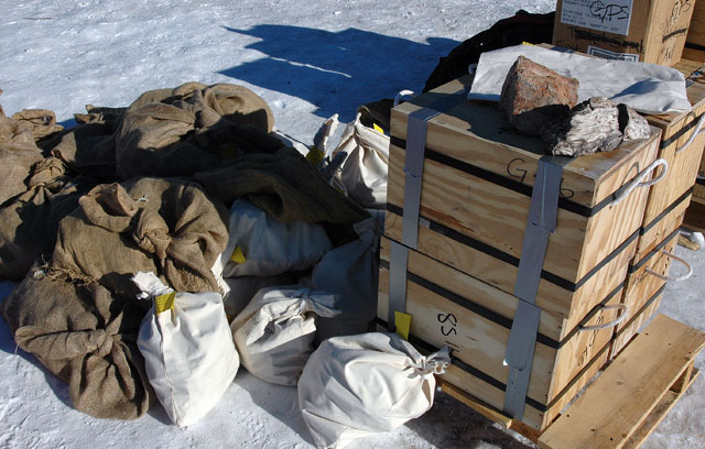 Bags and boxes sit on snow.
