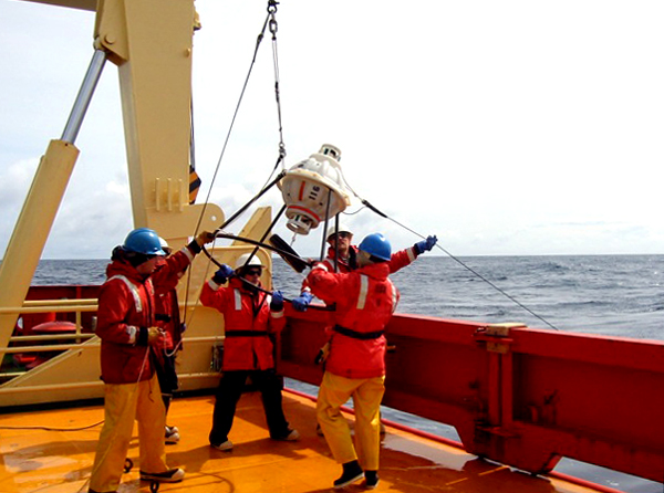 Scientists and ship crew deploy an oceanographic instrument.