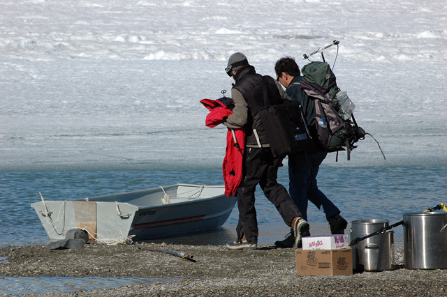 People carry equipment to small boat.
