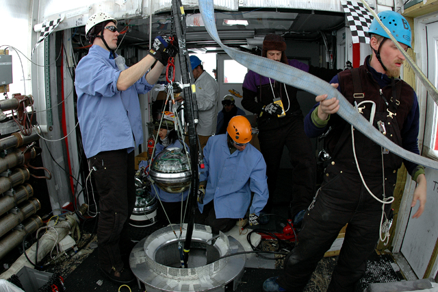 People prepare to lower instrument into a hole.