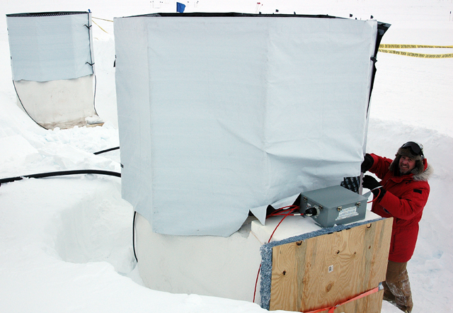 Person attaches curtain on top of snow pile.