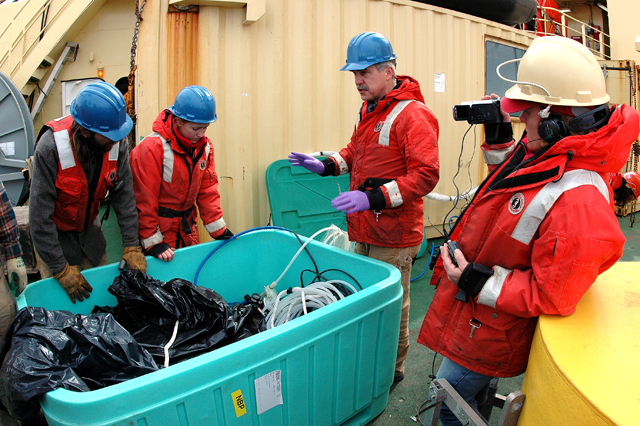 Scientists and ship crew peer into a box.