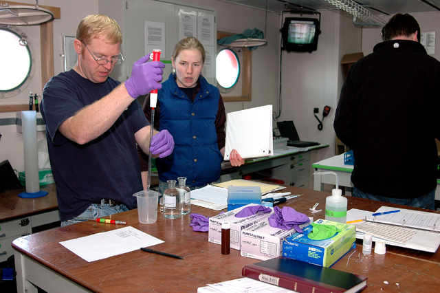 Scientists  work in a lab.