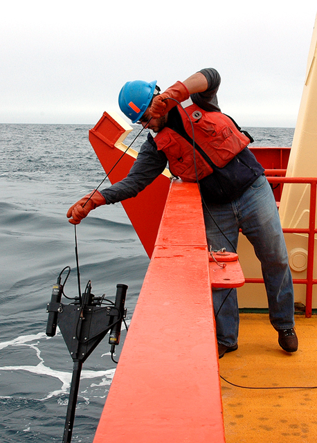 Scientist lowers instrument into the water.