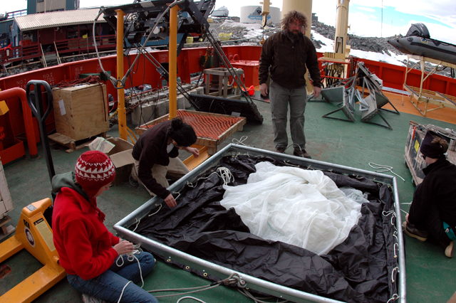 Scientists assemble net on deck of ship.