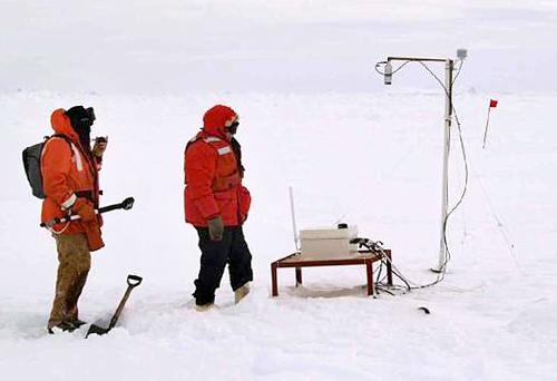 Scientists with instrument on ice floe.
