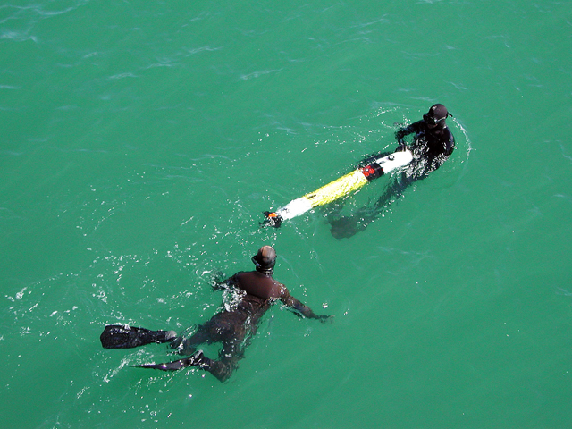Divers in the water with an object.