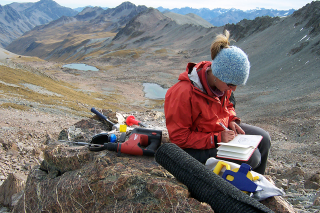 Woman sits on rock taking notes.