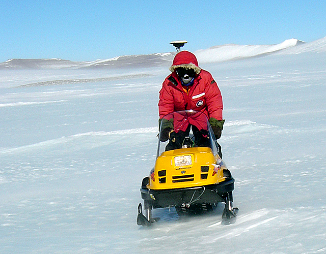 Scientist rides a snowmobile.