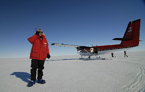 Man standing on ice with plane in background.
