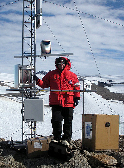 John Cassano next to an Automatic Weather Station.