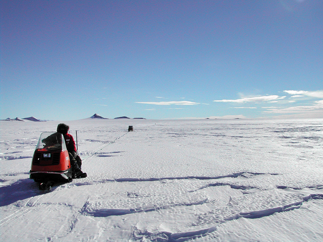 Person on snowmobile pulling an object.