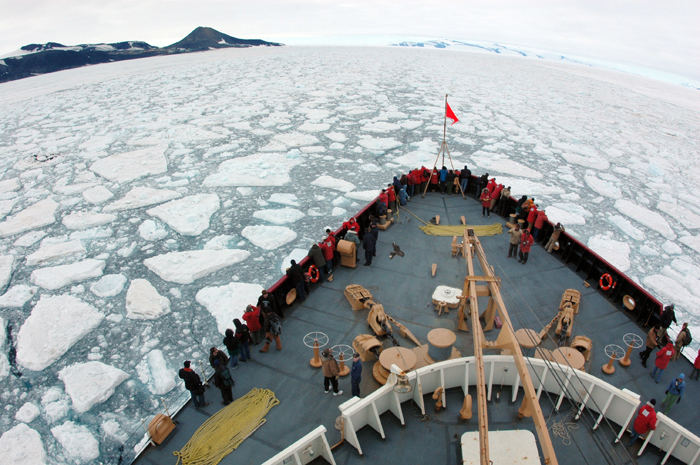 Bow of vessel pushes through sea ice.