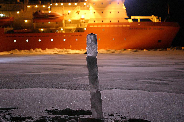 Cylinder of ice sticks up with ship in background.