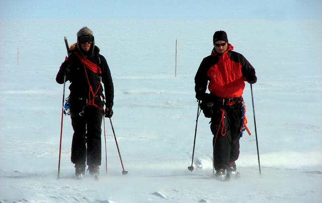 Two men ski on snow and ice.