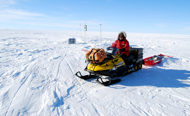 Scientist rides on a skidoo.
