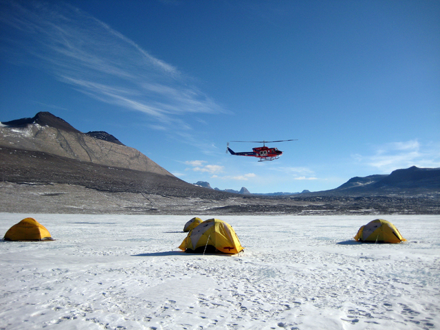 Helicopter flies over tents.