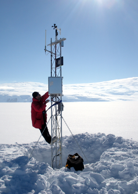 Scientist climbs on a weather station.