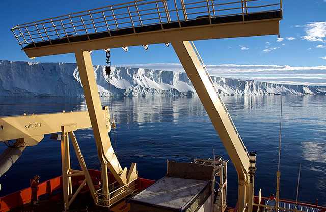 Stern of a ship with ice shelf in background.