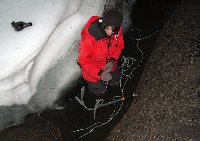 Person works with wire in snow cave.