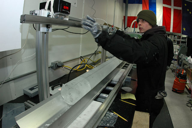Person operates machine that holds ice core.