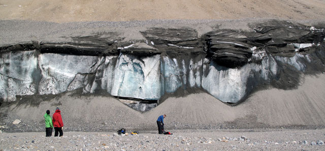People stand next to cliff of sediment and snow.