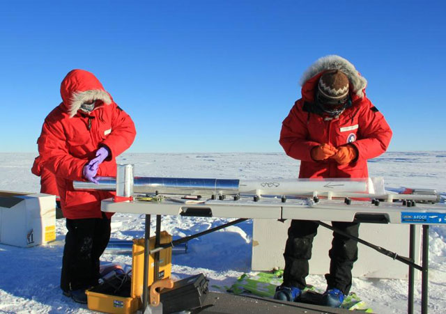 Two people handle an ice core on a table.