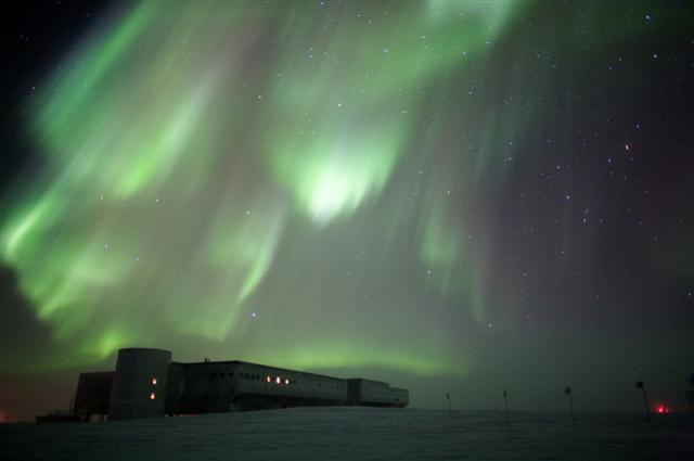 Aurora in the night sky above a long building