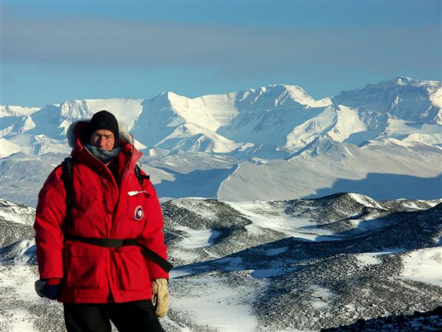 Person stands in front of mountain range.