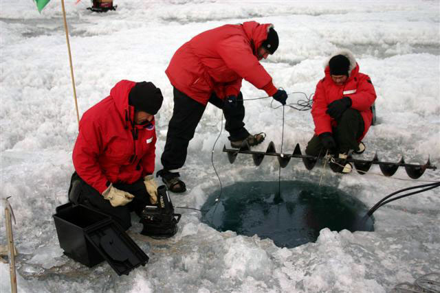 People drill a hole through ice.