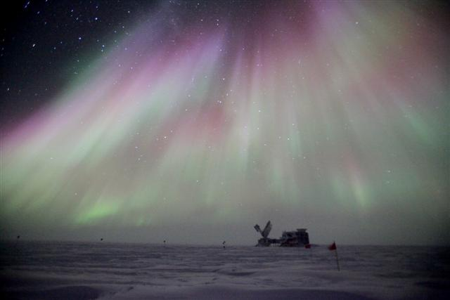 An aurora shimmers above a building on a plateau.