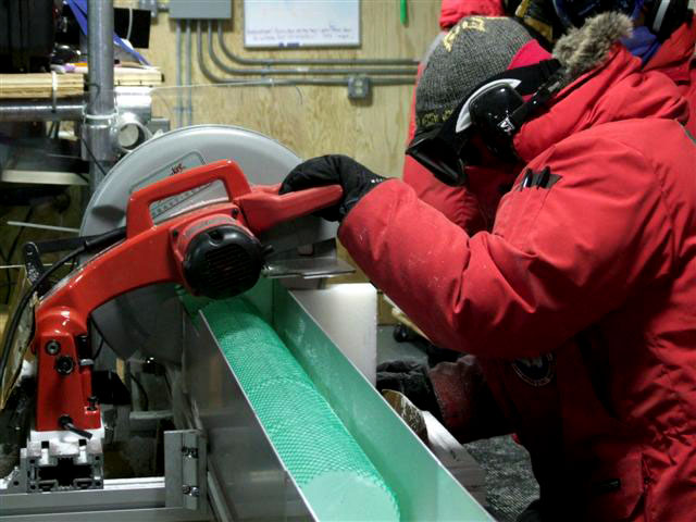 Person cuts chunk of ice with saw.