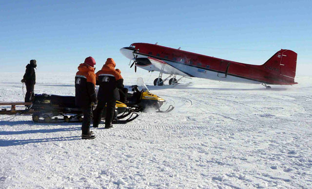 People stand near an aircraft on ice.