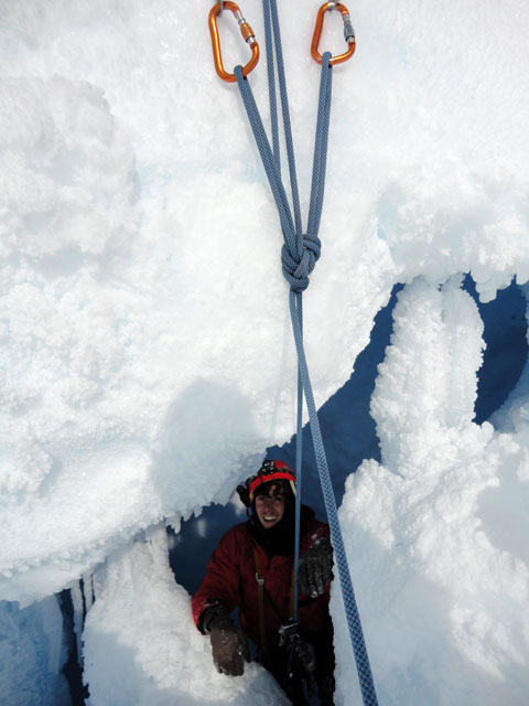 Person climbing into ice cave.
