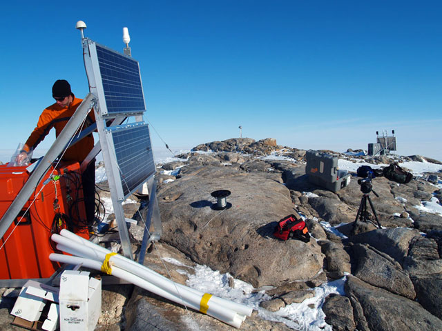 Person on rock cliff installs equipment next to solar panel.