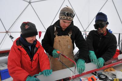 Three people examine an ice core.