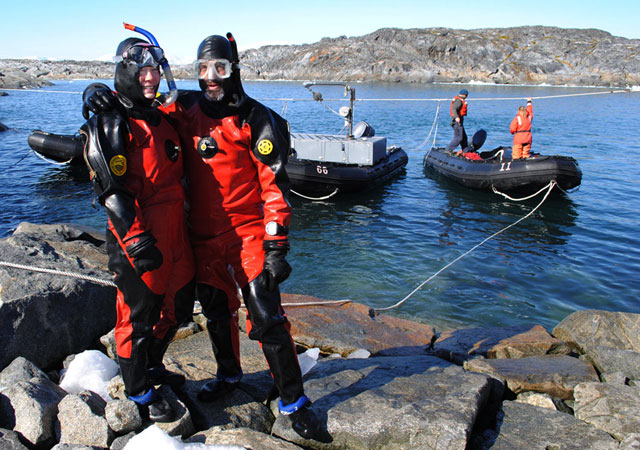 Two divers stand in front of water.