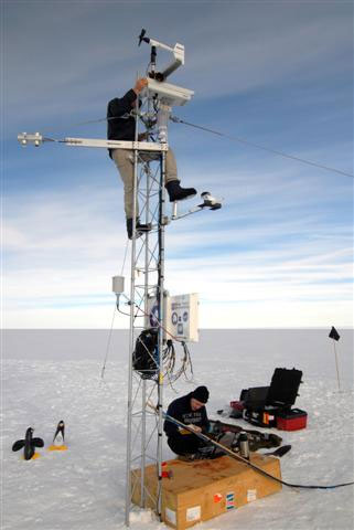 People work on tower set up on snow.