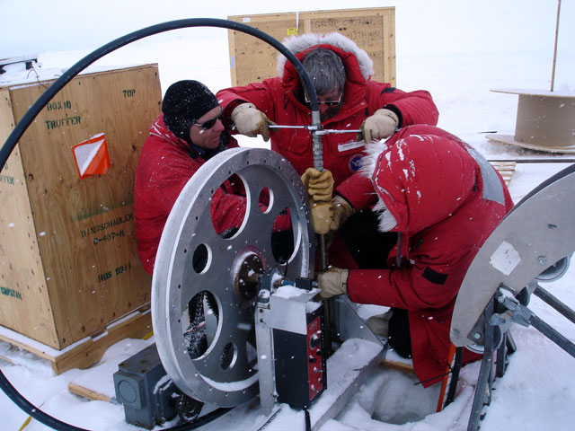 People work with instrument in snowy conditions.