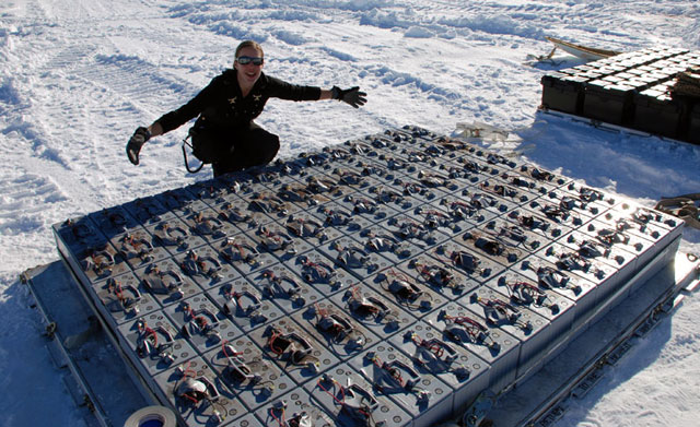 Person displays pallet of batteries.