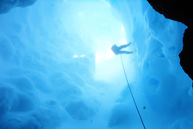 Person climbs down rope into ice cave.