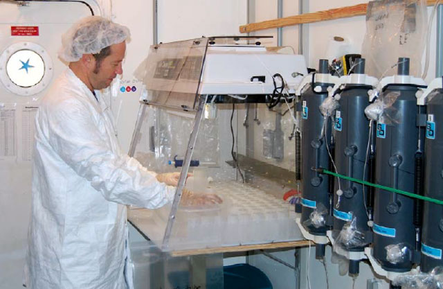 Man in sterile garb works in a lab.
