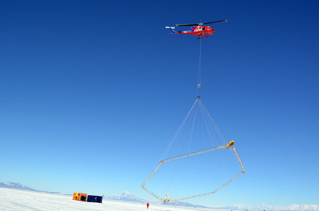 Helicopter carries instrument over ice.