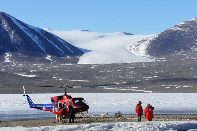 Helicopter and people in a snowy valley.