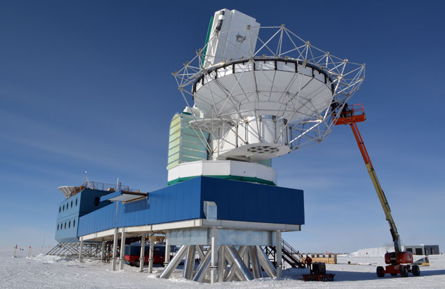 Workers assemble metal girder around telescope.